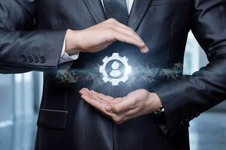 A businessman protects with a gesture a gear icon with a person on a blurred background.