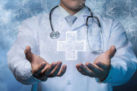 The concept of providing health care. Doctor shows a hologram of the Cross on a blurred background.