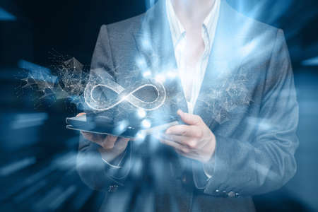 Unlimited Internet concept. Businesswoman shows infinity sign in tablet on blurred background.