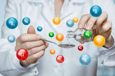 The doctor pours the medicine into a spoon containing vitamins.