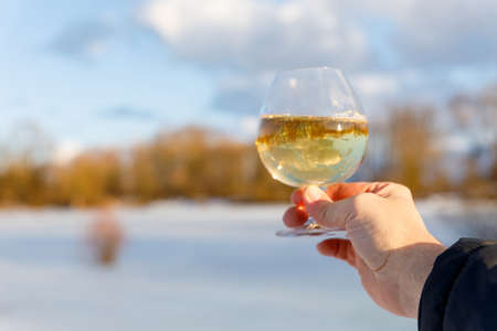 A glass of wine reflects the spring landscape on a blurred background.