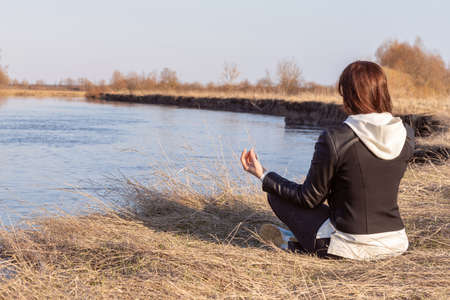 Woman meditates while sitting on the bank against the background of the river.