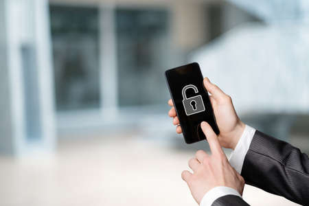 The concept of removing protection from a mobile device. The hand shows a mobile phone with an open padlock on a blurred background.