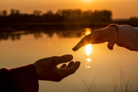 Hands reach out to each other against the backdrop of a sunny sunset.