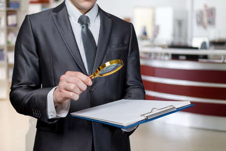 Criminal investigation study concept. Lawyer examining a document with a magnifier on a blurred background.