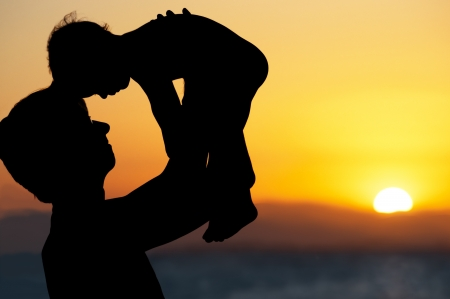 Father and little son - silhouettes on beach at sunset photo