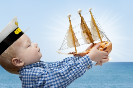 Portrait of the cute child  with the model ship photo