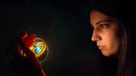 Fortune teller predicts future fate. The Gypsy holds a magic ball in her hand and wonders. Christmas divination. Esoteric and spiritualistic seance. The girl's face lights up the magic ball of fate.