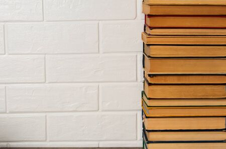 A stack of old books. Bookstore, library, bookshelf. Vintage, retro, antique.  Study, education, school, University. Literature, history, science. Books against a white brick wall. copy space Stock Photo