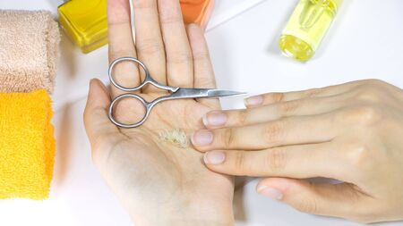 Manicure. A woman holds a cut-off nails in her hand. Cut your fingernails with small nail scissors. Trim your nails. Young woman taking care of her nails. Hygiene, clipping, cutter, self, procedure.