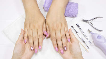 A woman shows her hands with painted nails. The manicurist holds the client's hands. Pink, Nude manicure, nail art, glitter Polish. Spa hand care. Beauty salon, hand massage. Feminine makeup.