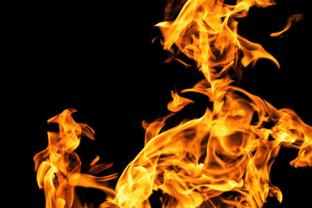 Fire flames on black background isolated. Burning gas or gasoline burns with fire and flames. Flaming burning sparks close-up, fire patterns. Infernal glow of fire in the dark with copy-space Stok Fotoğraf
