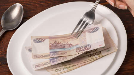 Russian rubles on a white plate. Keep money on the fork. Minimum subsistence level, food basket, minimum wage. Concept. Eat money, living wage. Economy. Crisis, inflation, business, Finance Banco de Imagens