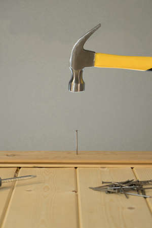 Hammer Hitting Nail On The Head. DIY. Carpenter hands with hammer wood and nail. Using hammer on wood backdrop. Tools for home repair. Fix the house. Close up of man hammering a nail into wooden board