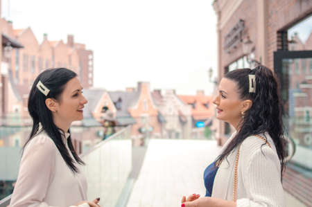 portrait of two young brunette women talking and laughing outside