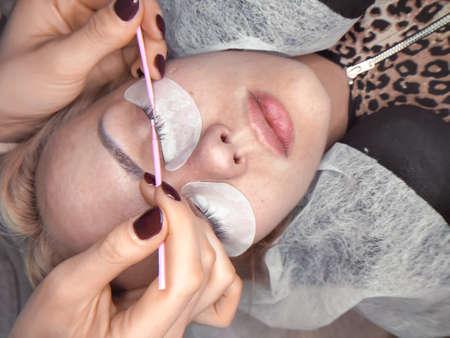 Lashmaker making lash extensions in beauty salon top view