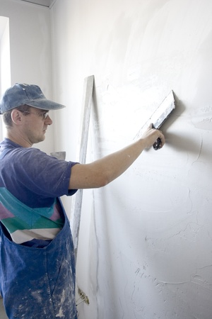 putty knives: plasterer inflicts layer of the puttying on wall