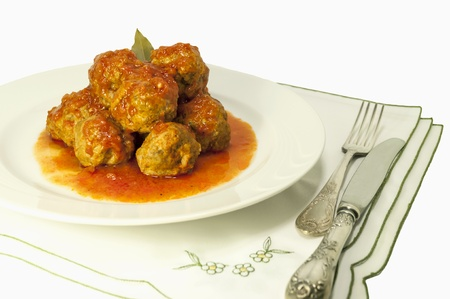 Italian meatballs on white plate with tomato sauce in fine dining setting isolated on white  photo