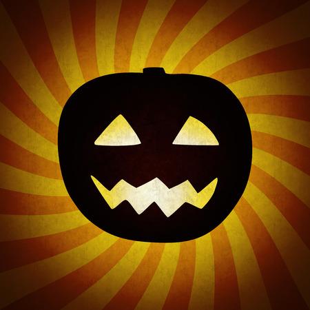 Grunge Halloween pumpkin on orange vintage background. Dark smiling Halloween pumpkin with shining eyes and mouth on the retro striped background with grunge texture.