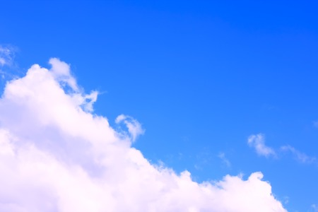 Blue sky with pinky white cloud, sunny day photo. Clear blue sky with a piece of cloud in light pink shade of white, nature background. Banque d'images