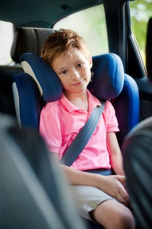 hapy: Portrait of hapy little boy sitting in car. Stock Photo