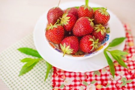 Fresh organic strawberry with mint garnish in white plate on cotton napkin on table