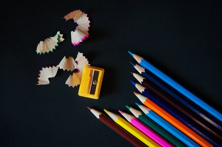 Colored pencils, sharpener and shavings on a black background Stock Photo
