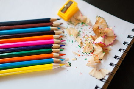 Colored pencils, sharpener and shavings on a notepad on a black background Stock Photo