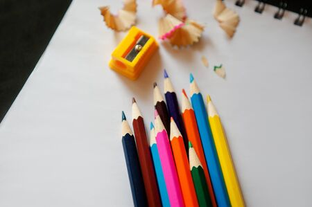 sharpened colored pencils, sharpener and shavings on a white notebook Stock Photo