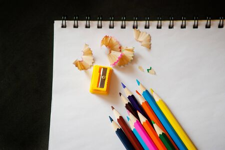 sharpener: sharpened colored pencils, sharpener and shavings on a white notebook Stock Photo