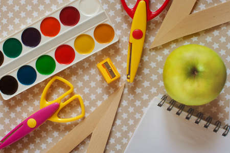 school supplies - ruler, paint, scissors, notebook and green apple on a beige background with stars Stock Photo