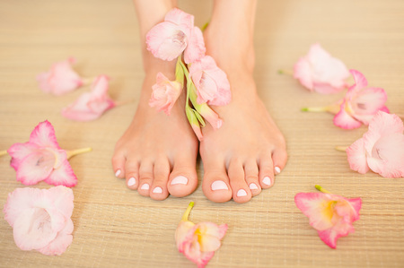 Spa composition - foot female with a light pink nails and pink flowers on a straw mat Stock Photo