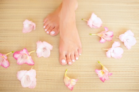french manicure sexy woman: Beautiful female legs. Beauty spa and skin care concept. Stock Photo