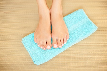 beautiful feet: Close-up shot of beautiful woman feet with French pedicure on blue towel Stock Photo