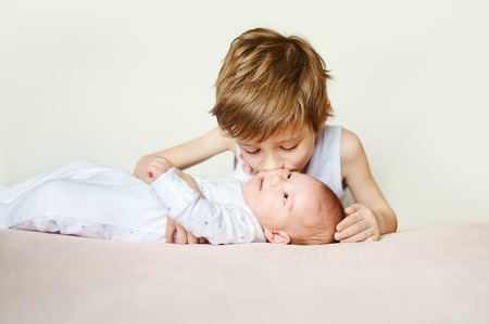 vernacular: baby in white pajamas lying on his back. Older brother kisses his. bright portrait