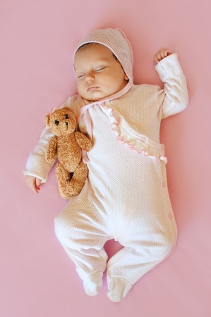 baby girl in white hat and pink pajamas hugging teddy bear sleeps in his bloodstream on a pink blanket Stock Photo