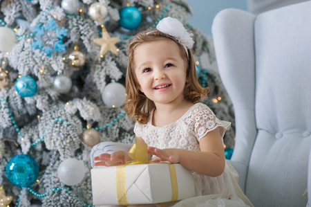 baby near christmas tree: Portrait of cute little girl smiling and holding boxes with gifts near the Christmas tree. New Year. Holiday fun. Happy baby . Merry . 2017. Delight from received
