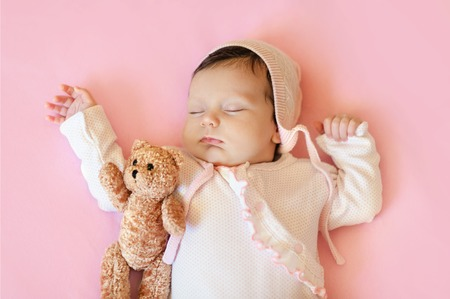 baby girl in white hat and pink pajamas hugging teddy bear sleeps in his bloodstream on a  blanket Stock Photo