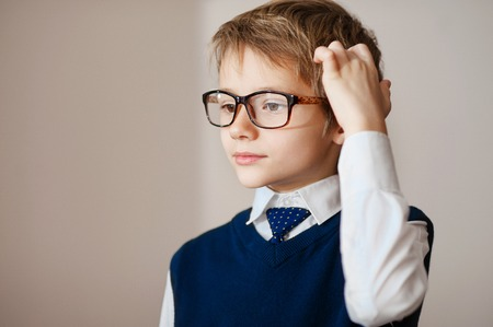 about age: Thinking child portrait of a little boy age seven in glasses  deeply about something looking up copy space above his head