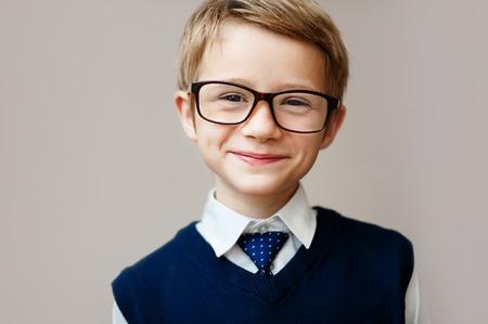 Primer plano de niño pequeño en uniforme escolar. Colegial feliz sonriendo y mirando a la cámara.