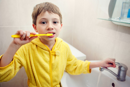 personal hygiene: Personal hygiene. Care of an oral cavity. The boy brushes teeth. Stock Photo