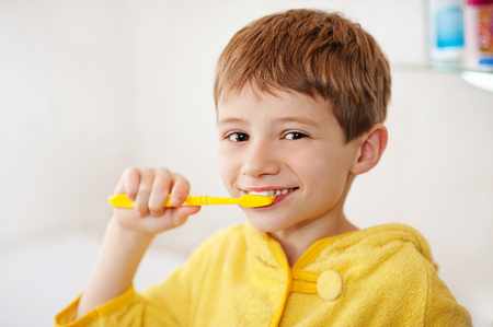 bathrobes: Beautiful kid preparing to brush their teeth wearing yellow bathrobes. closeup
