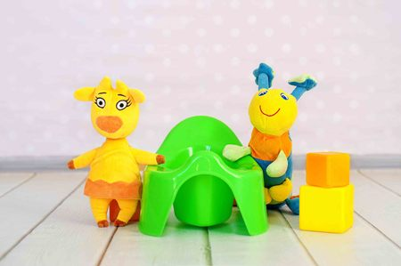 Green potty and toys on home interior background Stock Photo