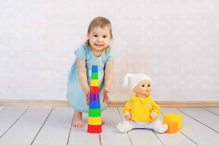 Cute little girl playing with toys sitting on the floor on wooden background