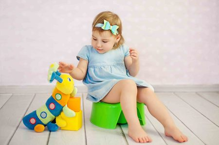 cute little girl potty trainting with a toy at house Stock Photo