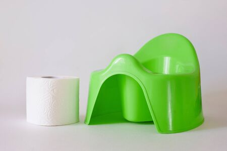 White toilet paper and stack of diapers beside green potty on white background
