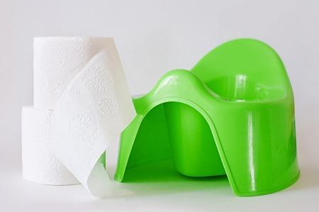 de groene pot en het toiletpapier van kinderen op een witte achtergrond Stockfoto