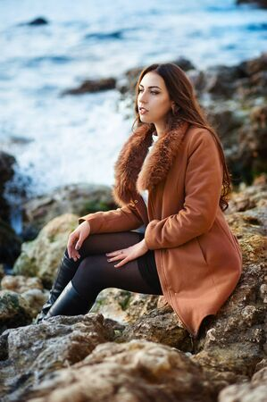 beautiful young woman in coat sitting sitting on stone seacoast