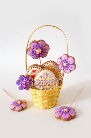Little Easter is on a festive scarf. Multi-colored Easter eggs lie in a basket with decoration gingerbread