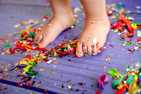childrens birthday party. bare feet are on the floor with confetti Stock Photo